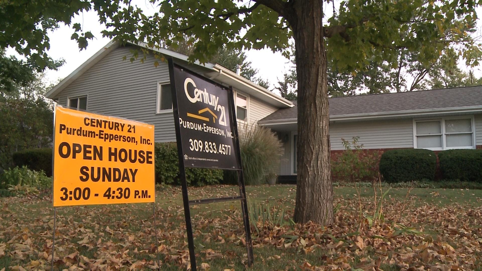 "A ""for sale"" and ""open house"" sign sits in front of John Nelson's home on Franklin Street in Macomb. Nelson says he's lowered the price twice since the home has been on the market for a year."