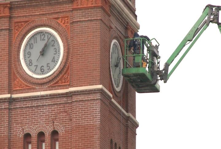 Close up of crews working on the clock tower.