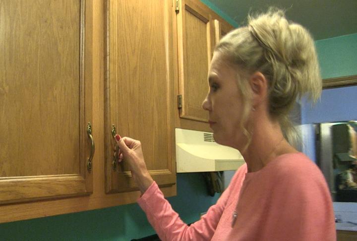 Jeana Shepard closes a cupboard in her kitchen.
