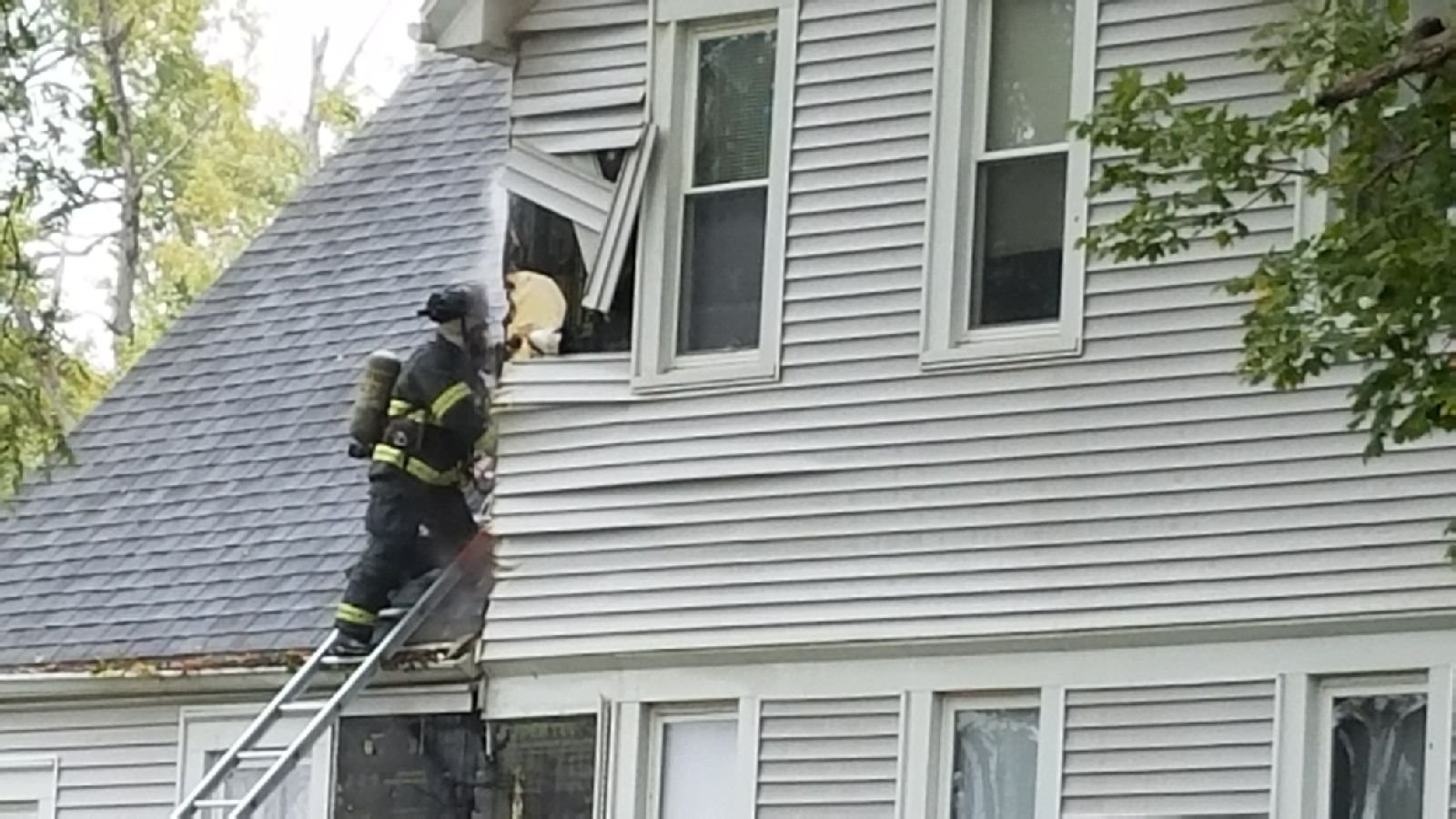Firefighters taking off siding as they ensure the fire is put out.