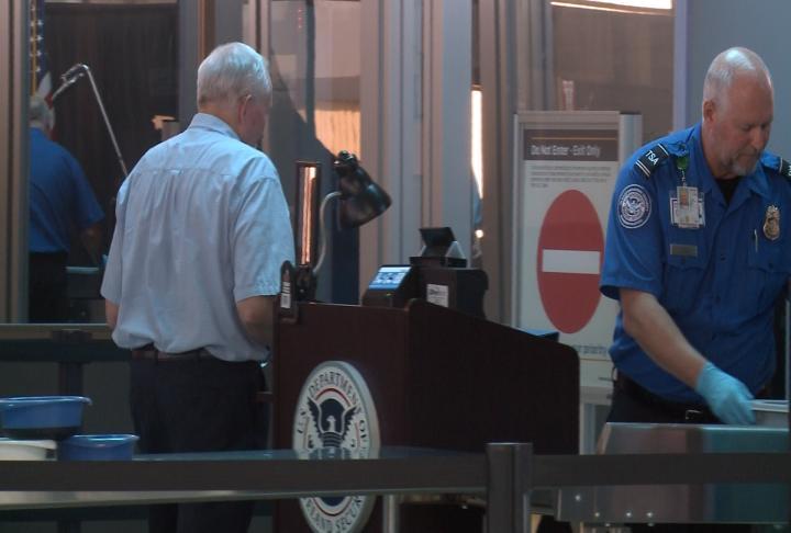 Passenger begins security check for flight.
