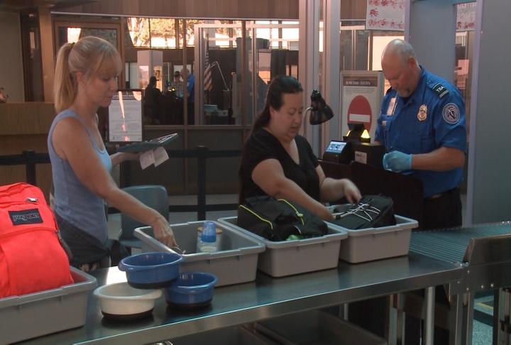 Passengers prepare to go through security.