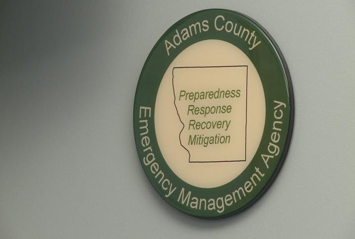 Adams County Emergency Management sign hangs in an office.