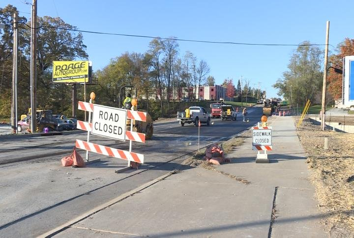 A road closed sign sits in the road where crews work to finish a bridge replacement.