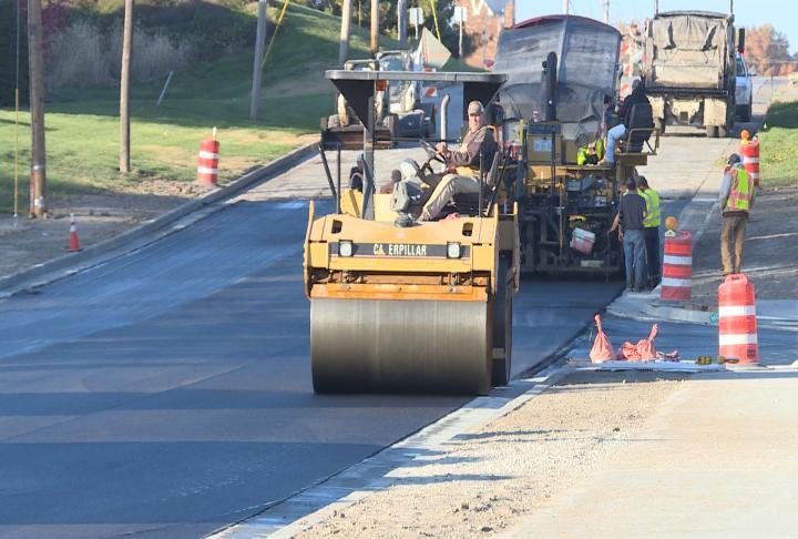 Worker drives a roller along the asphalt.