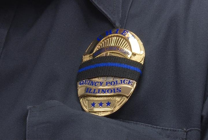 Quincy Police Department badge being worn by an officer.