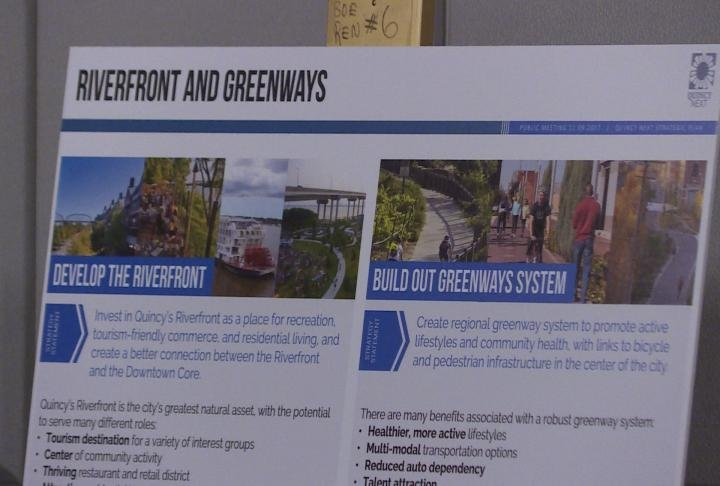 Board displays details on the riverfront and greenspace plans.