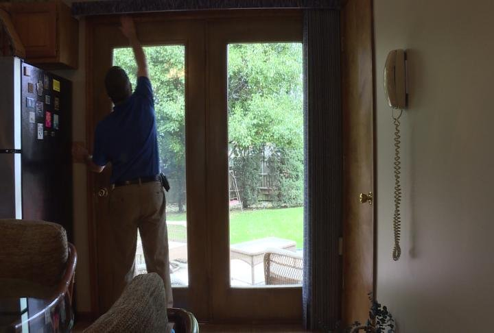 Ameren official checks the sealing around a sliding glass door.