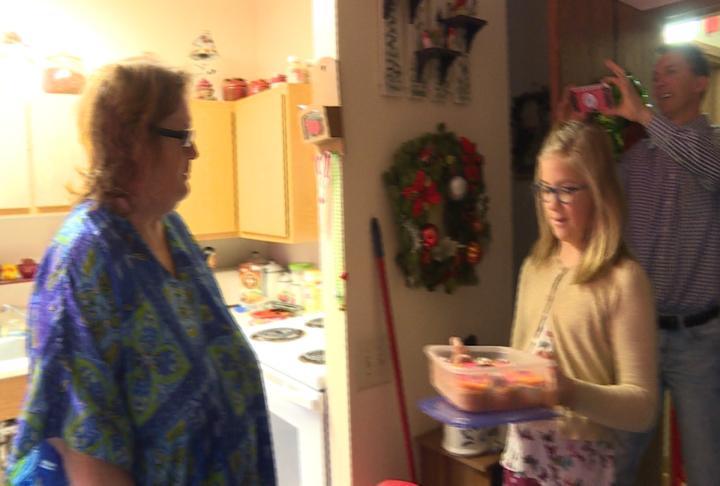 A Meals on Wheels volunteer delivers food to Linda Oliver.