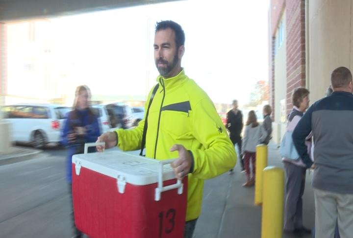 A volunteer grabs a cooler full of food to deliver.