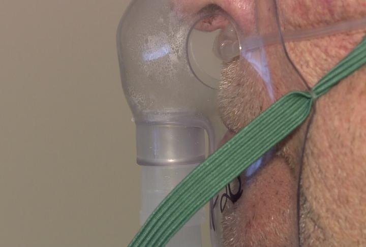 A patient wears a mask that helps deliver medicine.