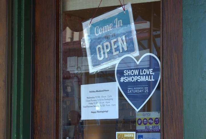 Open signs hang in the window also promoting Small Business Saturday.