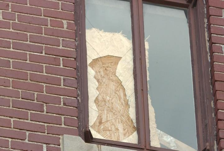 Several windows at the old hospital are broken out and boarded up.