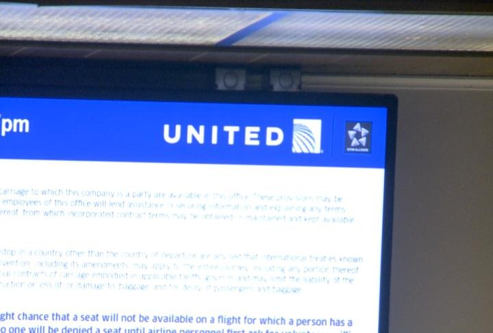 Video screens display the United logo ahead of the flight service change.