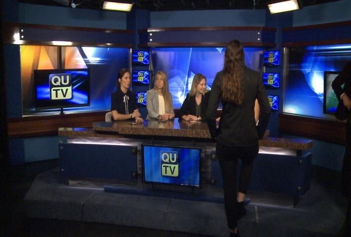 Students talk while sitting on the new QUTV set.