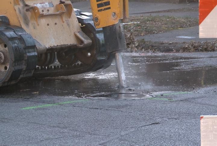 Crews drill into the ground to find source of water main break.