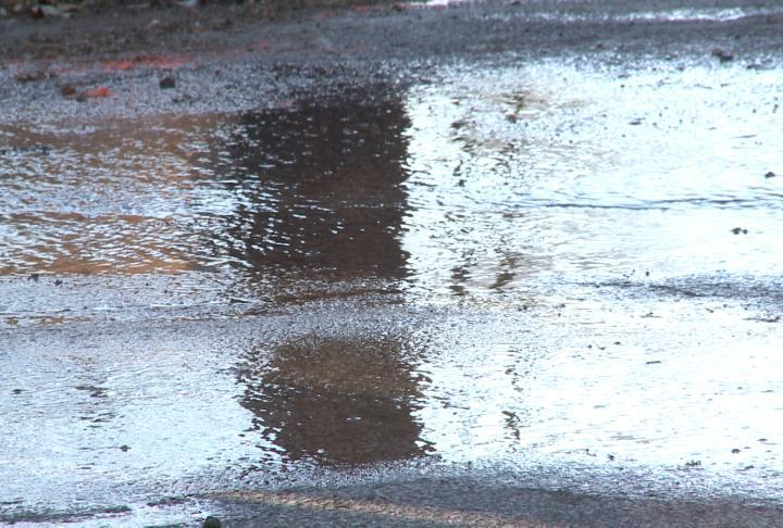Water covers the street near a water main break.