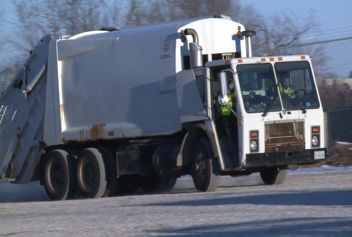 Workers drive garbage truck.