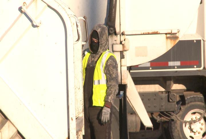 City worker looking around garbage truck.