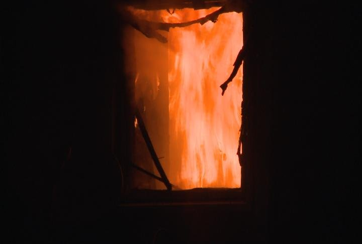 Flames damage a window and spread inside this home on Mulberry Street in Warsaw, Illinois.