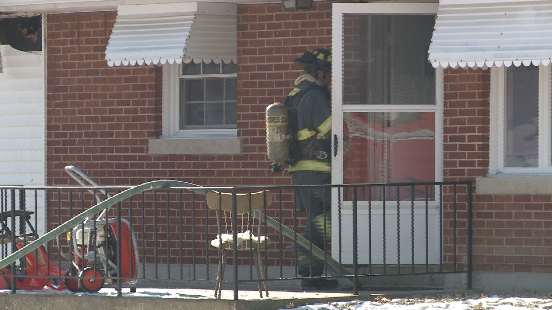 Firefighter goes into the home.