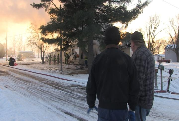 The homeowner looks on as his house burns to the ground.