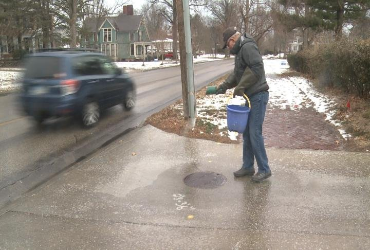 Residents Bob Moore putting down salt on his driveway