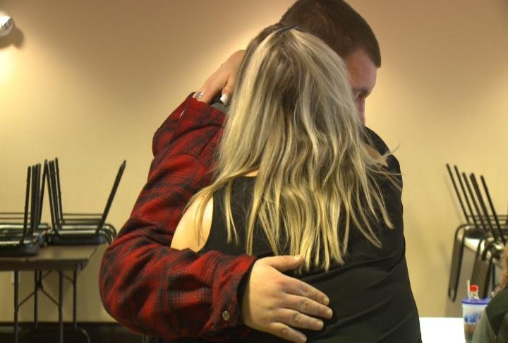 Cory Earnst hugs a family friend, grieving his mother's passing.