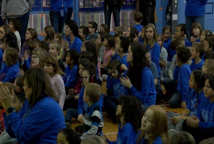 Faculty and students cheer after learning the news about the Lighthouse School distinction.