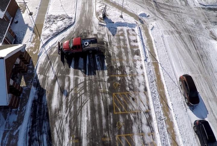 A shot from the WGEM News Drone of a snowplow clearing a parking lot.