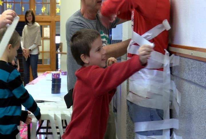 A student takes his turn taping his principal to a wall.