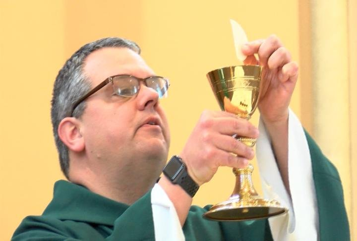 Father Chris Comerford presenting communion sacraments
