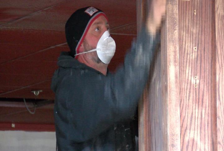 Owner David French sanding down wood inside the restaurant.