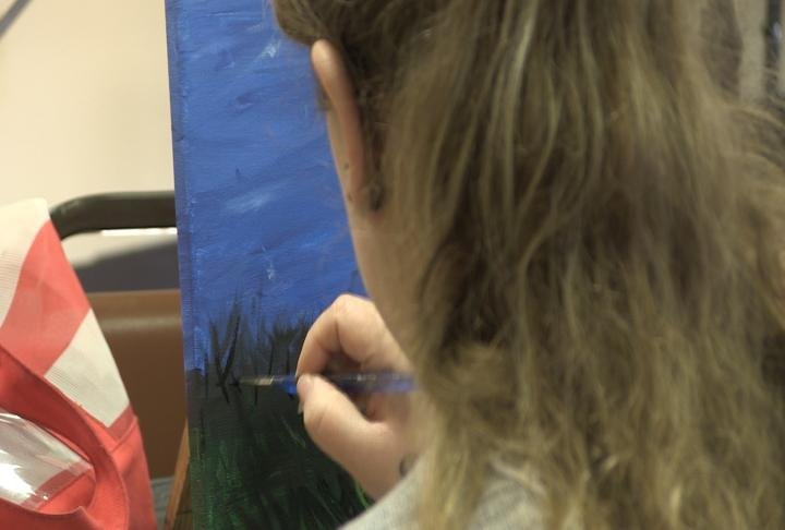 One attendee works on her painting.