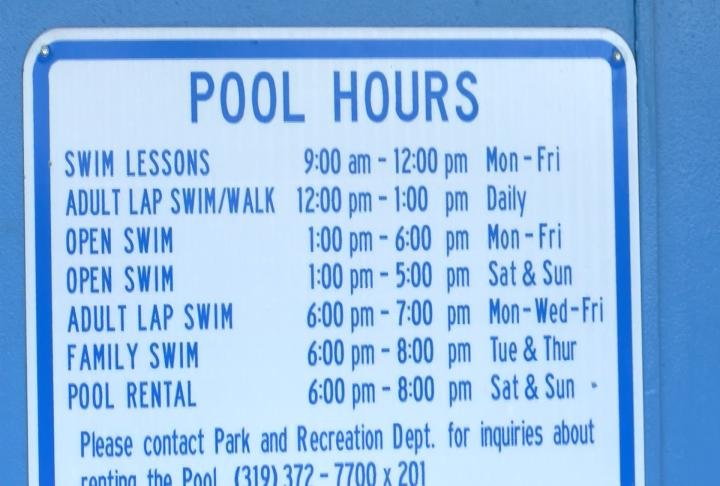 Pool Hours posted at the city pool.
