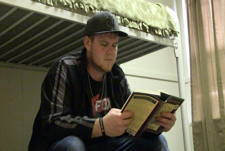 Heroin addict Austin Chitwood reads in his room.