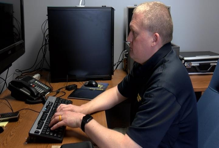 An officer working on extracting data from a device.
