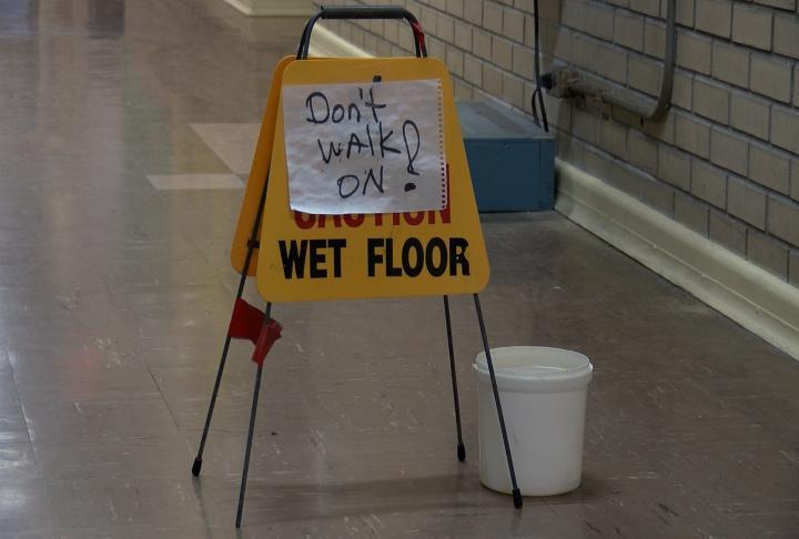 Buckets in the hallway catch water.