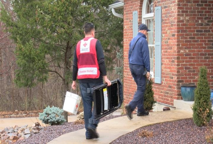 Volunteers with firefighters installing smoke alarms.