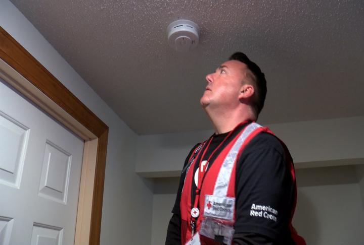 Baden checking the status of a smoke alarm.