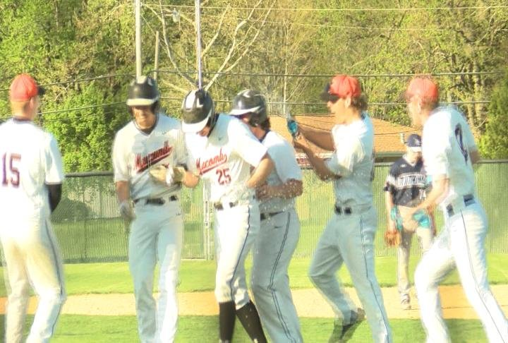 Macomb mobs Ben Higgins following his walk-off RBI single to beat Monmouth-Roseville.