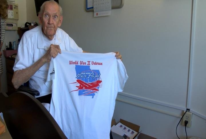 Osberg holding up his honor flight shirt.