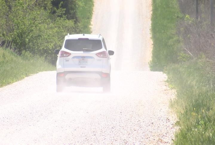 A car driving on a gravel road creating dust.