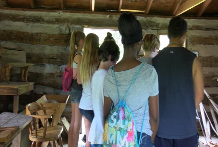Students learning about the Log Cabin Village.