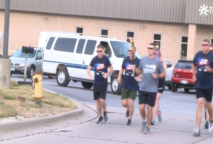 Quincy Police officers leaving Transitions with the torch.