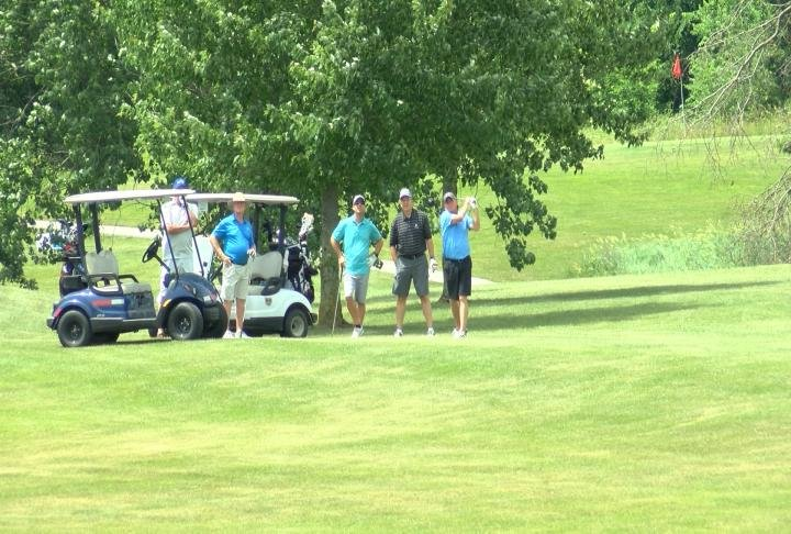 A team hitting their approach shot at Norwoods Country Club