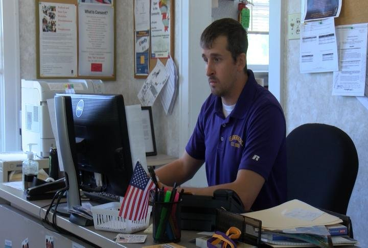 Brian Kauth sits at his desk at the WIU Veterans Resource Center
