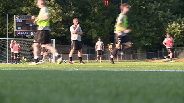 QU head coach Mike Carpenter looks on as his team practices at Mackenzie Field for the first time on Saturday night.