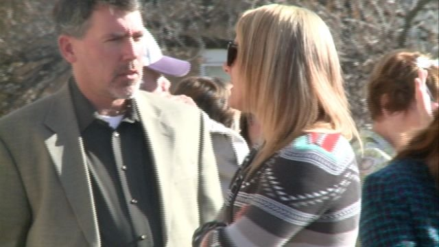 Arnett's daughter  stands outside after hearing