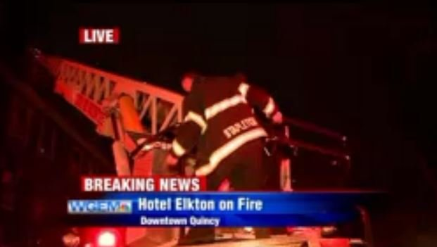 A firefighter helps an occupant down the ladder